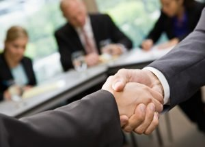 Picture of two people shaking hands in office